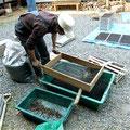 よく乾かした「稲育苗用培養土」を篩(ふるい)に掛けて、大きな土の固まりを取り除き、砕いて小粒の土に仕上げます。