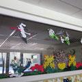 Vaikų išpjaustyti, iškarpyti ir nuspalvinti karpiniai puošia klasės langą.