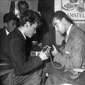 Charles Pater en Rudi Contini Selier (de gitarist van Pim Maas) wisselen gitariteiten uit tijdens de finale van de Elvis wedstrijd in de Royal. Op de achtergrond kijkt Roek Williams = Willemze (met Buddy Holly bril) toe.