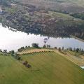 vue aérienne du lac de la Thésauque avec montgolfières près des Gites des Camparros à Nailloux