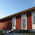 Eingangsbereich zu unserem Musterhaus für natürliches Bauen, Gestaltung mit Natursteinen und Lärchenholz