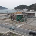 女川町立病院から見た、津波で倒壊した江島共済会館。後方の2階建てビルは七十七銀行女川支店