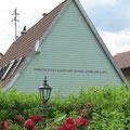 """Sprichwort in Keramikbuchstaben am Hausgiebel: """"denn die Blume macht den Garten, nicht der Zaun"""""""