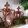 Zwei Edelrostkronen mit Moos und Glaseichhörnchen dekoriert.
