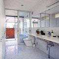床・壁を白タイルで仕上げた洗面所から浴室へのつながり