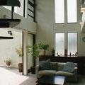二連の窓から明かりが射し込む、開放的な吹き抜けのリビング