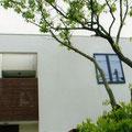 白壁と濃茶にペイントした目隠しガラリがアクセントの建物外観