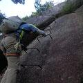岩に打たれたハシゴを登る写真。