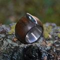 """Ring aus Silber, <a href=""""./glossar/"""" >rhodiniert</a>, mit einem Mantel aus grünlich-braunem <a href=""""./glossar/"""" >Pockholz</a> und einem grünen<a href=""""./glossar/"""" >Turmalin</a>-<a href=""""./glossar/"""" >Cabochon</a> in<a href=""""./glossar/"""" >Navette</a>form"""