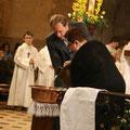La cuve baptismale est remplie d'eau par deux parrains