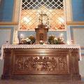 Autel en bois sculpté représentant la Cène ; derrière l'autel, on aperçoit la statue de Notre-Dame de Lorette dans l'arrière-chapelle
