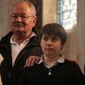 Au moment du baptême, le parrain pose sa main sur l'épaule de son filleul.