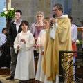 William et Natacha, revêtus du vêtement blanc sont entourés de leurs parrains et marraines et du P. Loïc qui vient de les baptiser