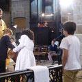 Deux enfants versent l'eau qui servira au baptême dans la vasque baptismale