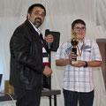 Daniel Messer nimmt den Pokal von Chairman Norbert Heil entgegen