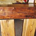 Naturholz-Kante der massiven Holzplatte und die beiden Balkendes Tischgestells
