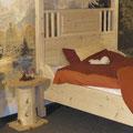 """Kopfteil des Himmelbetts """"Gemütlichkeit"""" mit senkrechten Verstrebungen und eingefrästem Spruch, daneben Nachttisch aus einem Stück Baumstamm und Holzplatten"""