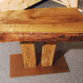 Couchtisch mit ca. 10 cm starker Holzplatte, zwei leicht schräg gestellte Balken auf einer rechteckigen Stahlplatte als Tischgestell