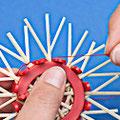 Die Legeform wieder umdrehen. Alle Halmbündel im Uhrzeigersinn umwickeln und binden, als erstes das Bündel rechts des bereits verknoteten Bündels: Den Faden hinter dem Bündel entlangführen und zwischen den Bündeln nach vorne holen, ...