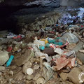 The entrance of the cave is full of waste.