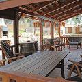 Vista del porche con 3 zonas diferenciadas: mesa comedor, barriles para hacer el aperitivo, conjunto sillas para relajarse y charlar.