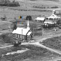 Vue aérienne de l'église de Mashteuiatsh, du monastère des Oblats ainsi que de leur ferme. Année inconnue. Collection Jean Gagnon.
