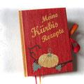 """""""Meine Kürbisrezepte"""" - Harcovereinband, Format 16cm x 22cm x 3cm, 100 Blatt/200 Seiten wechselnde Lagen von rotem und orangefarbenen Papier, sowie Lesebändchen und Schleifenverschluss in der gleichen Farbe."""
