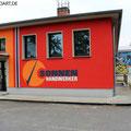 Sonnenhandwerker fassadengestaltung mit Wandbild und Firmenlogo gestaltet in Fürstenwalde mit der Graffiti Kunst im schönen Brandenburg Oder Spree.Immobilien verschönern