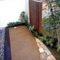 坪庭。土舗装と枕木による構成、アクセントに石張り