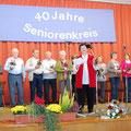 Im Vordergrund bedankt sich Roswitha Brunn bei den vielen Mitarbeitern, die durch Unterstützung vor und hinter den Kulissen immer wieder zum Gelingen der Seniorennachmittage beitragen.