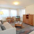 Wohnzimmer mit TV, Bettsofa, Esstisch und kostenlosem WLAN-Internet