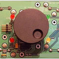 <b>Leiterplatte</b><br />Auf der Rückseite sind vier AA-Batterien montiert. Unter dem abnehmbaren Drehknopf: ISP-Steckverbinder und Einspeisemöglichkeit bei erschöpften Baterrien. Links Steckverbinder für Elektromagnet