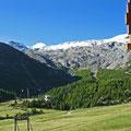 Hausrand und Blick auf Piste sowie Bergwelt