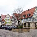Fachwerkhäuser und Brunnen in der Altstadt von Mönsingen.