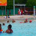 サンタ帽をかぶった人たちがプールで遊んでる~。