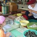 Siena beobachtet gespannt eine Marktfrau beim Öffnen von Muscheln