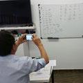 Fermín, inmortalizando en su mobil una tabla de compensación de exposicion. Curso básico de fotografía Digital. Foto: Andreu Gual