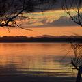 Bäume und Büsche links und rechts rahmen die in das warme Licht des Sonnenuntergangs getauchte Landschaft ein.