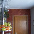 Die Effektwand in der Küche wurde gestaltet mit einer Kalkpresstechnik in dunkelrot und überarbeitet mit goldenem Wachs.