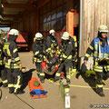 Verletzter Atemschutzgeräteträger wird aus dem Gefahrenbereich gebracht