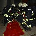 Verunglückter Atemschutzgeräteträger wird auf das Tragetuch gelegt