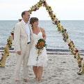 """Foto: """"Hochzeitpaar am Strand vor Blumengirlande nach Hochzeitszeremonie"""""""