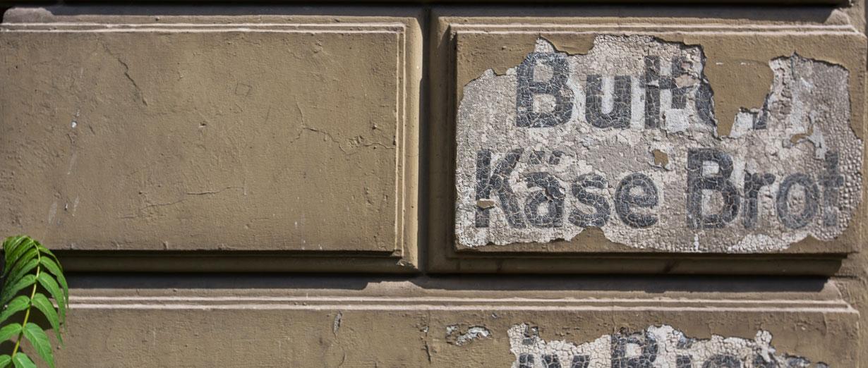 Verwitterte Inschriften an einer Kreuzberger Hauswand.