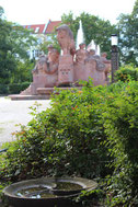 Vogeltränke und zwischen alten Bäumen der Fruchtbarkeitsbrunnen mit hohen Wasserfontainen. Arnswalder Platz. Foto: Helga Karl