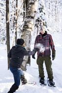 Photo de deux collègues faisant une bataille de boules de neige en hiver pendant un team-building dans les cantons de l'Est au Québec pour Évasions Canadiana par Marie Deschene photographe pour Pakolla