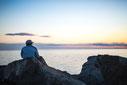 Photo femme assise sur rochers devant coucher de soleil Bas-Saint-Laurent Rimouski Québec Canada été fleuve par Marie Deschene photographe Pakolla