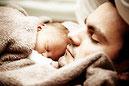 Vater mit Säugling geborgen kuschelnd