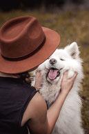 Halterin mit Fedora Hut hält das Gesicht Ihres Hundes fotografiert von der Ostschweizer Hundefotografin Monkeyjolie