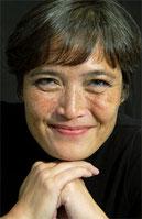 Sandra Wöhe blickt direkt in die Kamera, lächelnd, Kinn leicht auf die Hände gestützt