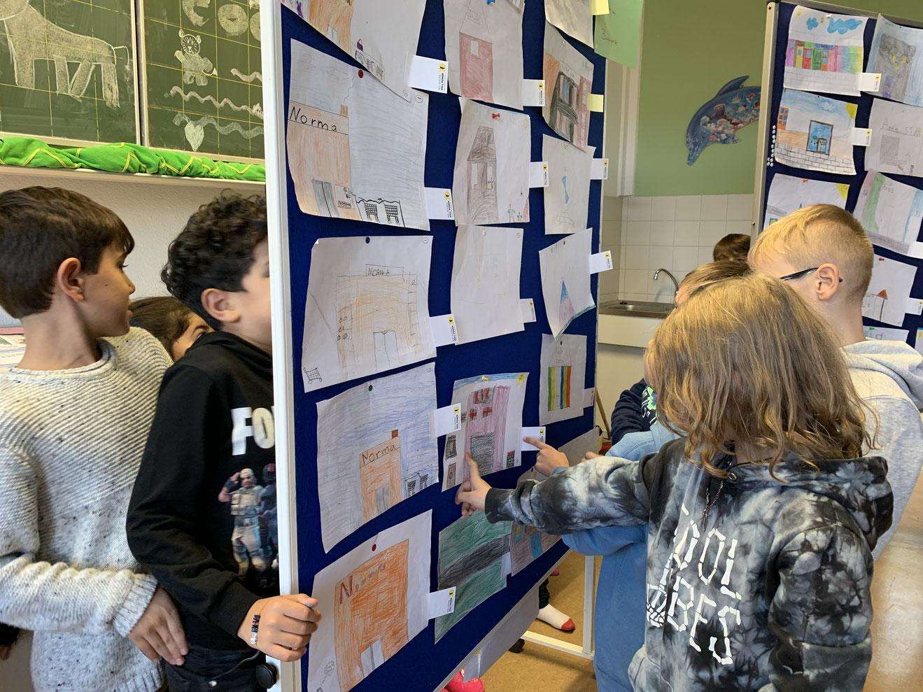 Kinder der Offenen Ganztagsschule Kopernikusstraße in Buchforst sichten die Bilder ihrer Schulkamerad*innen.
